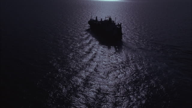 aerial. moving over ocean water towards freighter ship sailing from right to left. moon reflecting off water. camera passes over ship. - ship stock videos & royalty-free footage