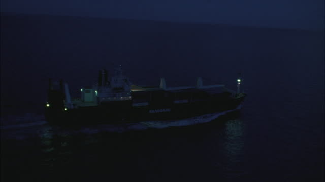 wide angle of freighter ship driving from left to right in ocean. gray clouds. - cargo ship stock videos & royalty-free footage