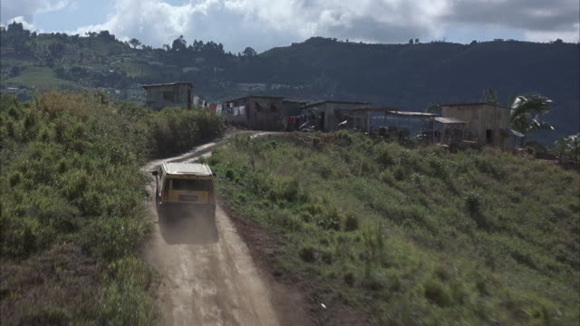 aerial. following yellow hummer and old blue truck driving along dirt road to community of shack-like houses in lush green mountains. could be cuba. camera passes over cars and continues to pass over village. - hummer stock videos and b-roll footage