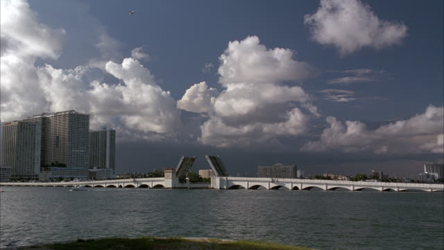 wide angle. bridge in miami with drawbridge in foreground. drawbridge is up. sailboats in fg. high-rise office or apartment buildings on left. cumulus clouds in sky. high-rise buildings in distance. - drawbridge stock videos and b-roll footage