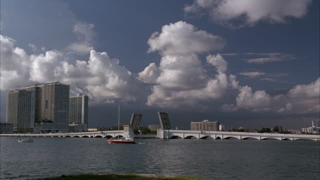wide angle of bridge with drawbridge in foreground. drawbridge is up. sailboats in fg. high rises in bg. cumulus clouds in sky. other high rise buildings in background. - drawbridge stock videos and b-roll footage