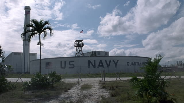 """wide angle. pan right to left of outside of naval base. see """"us navy guantanamo bay"""" written on side of wall. guard tower behind wall with american flag extended on top. barbed wire fence surrounds base. see sign that says """"mines/danger"""" in foreground. - cuba stock videos & royalty-free footage"""