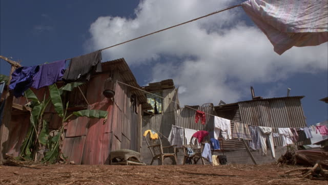 up angle of shacks in slum village on side of hill. see clothesline extended across shot. yellow hummer h2 breaks through one of the shacks causing shack to explode into pieces. explosions. - bassifondi video stock e b–roll