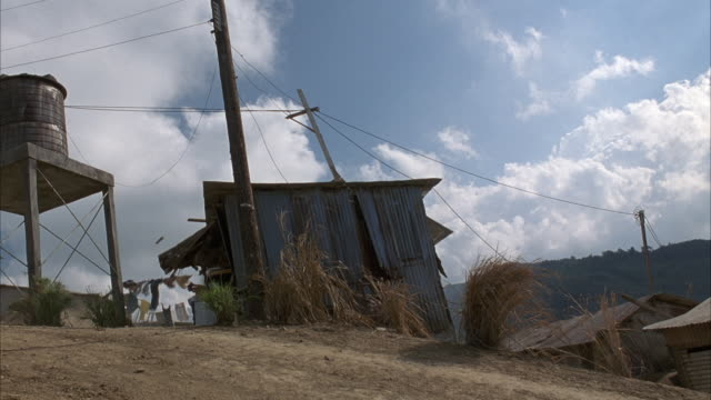 est wide angle of wooden shack on top of hill. see telephone pole and small water tower next to shack. yellow hummer h2 drives through shack from left to right, tearing shack to pieces. mountains in background. - hill点の映像素材/bロール