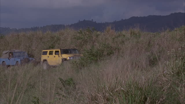 wide angle of yellow hummer h2 and blue truck driving through grassy terrain from background. shot pans right quickly to military truck filled with soldiers driving from frame right. soldiers jump out and start shooting at hummer and blue truck as they dr - hummer stock videos and b-roll footage