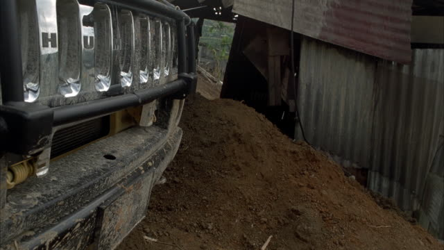 close angle of hummer h2 radiator grille driving down dirt road. side angle. see mountains and palm trees in background. - hummer stock videos & royalty-free footage