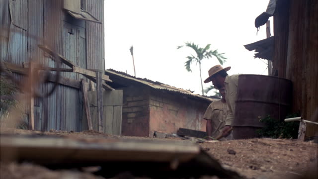 pan left to right. begins with medium angle on two men sweeping around wooden shacks. men suddenly look up and run. yellow hummer h2 is driving through shacks, knocking down houses, and passes shot from left to right. shot pans back and forth. see militar - hummer stock videos & royalty-free footage