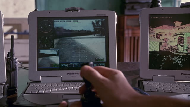 MEDIUM ANGLE OF MAN'S HAND PLAYING WITH JOYSTICK CONTROLLING A REMOTE CONTROL TRUCK SHOWN ON SCREEN IN FRONT. THREE SMALL COMPUTER SCREENS SET ON TABLE IN FRONT. MIDDLE SCREEN SHOWS REMOTE CONTROL TRUCK DRIVING AROUND, BEING CONTROLLED BY MAN MANEUVERING