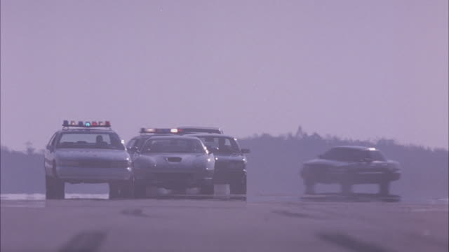 WIDE ANGLE ON A SILVER FERRARI 575M MARANELLO CHASED BY NUMEROUS POLICE CARS AND OTHER TRUCKS AND CARS ON A RUNWAY. DRIVING TOWARD CAMERA. POLICE CARS OVERTAKE FERRARI AND TRY TO STOP IN FRONT OF FERRARI.