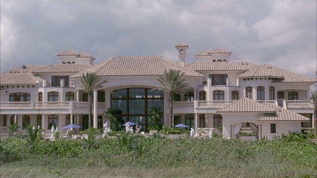 WIDE ANGLE OF LARGE BEACHSIDE MANSION. OVERCAST DAY. POV FROM BACKYARD. SEE POOL IN BACKYARD.