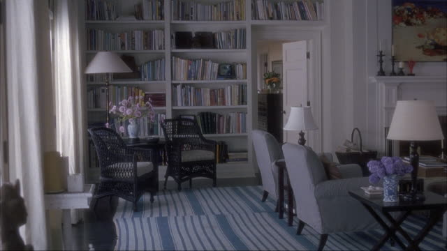 vídeos de stock, filmes e b-roll de medium angle. living room. blue and white throw rug on the floor. four lounge chairs and coffee tables. bookshelves built into wall. room painted white. the hamptons, long island. - esetante de livro