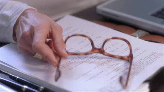 close angle. insert of woman putting eyeglasses down on stack of papers. tortoise shell frames. only hand of woman visible. - putting stock videos & royalty-free footage