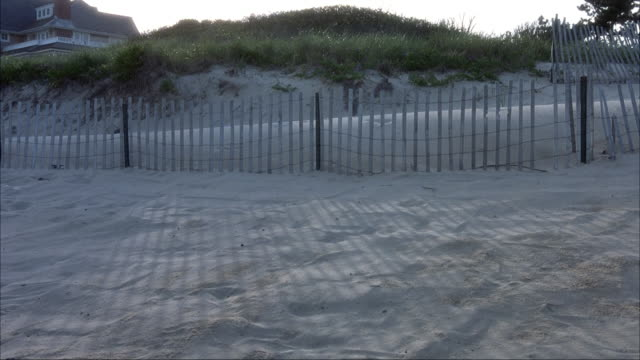 vidéos et rushes de wide angle shot of beach sand with fence and beach house in bg. - long island