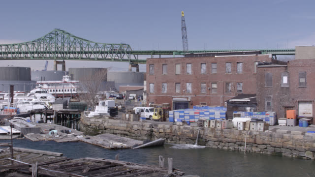 wide angle vignette of shipyard, port, or harbor near bridge. could be bay. warehouses with cargo.  maurice j. tobin memorial bridge (mystic river bridge). - san francisco oakland bay bridge stock videos and b-roll footage