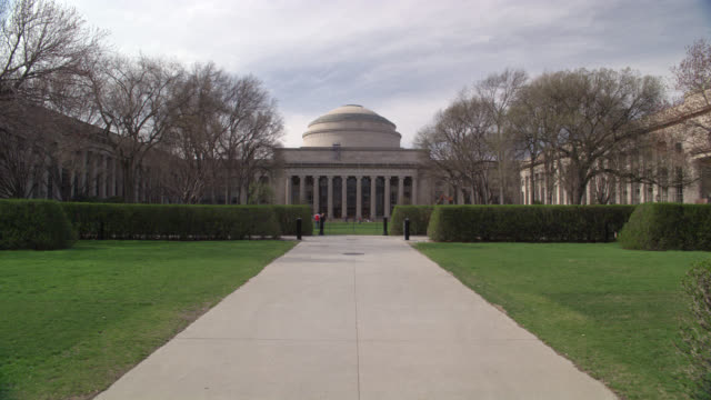 wide angle of university or college campus dome building. shrubs line the walkway to building. could be library or courtyard. mit great dome and killian court. - wide stock videos & royalty-free footage