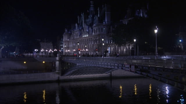 est wide angle. pon saint-michel bridge over the seine river. town hall of paris lit in bg. a lit riverboat sails from l-r down river through bridge. - seine river stock videos and b-roll footage