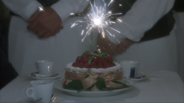 vidéos et rushes de medium angle of cake on table with sparkler in the middle. waiter's hand lights sparkler with lighter. two waiters standing behind cake with hand crossed. only shoulders down visible. three coffee cups on table with cake - dessert