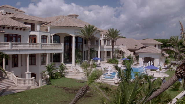 vídeos de stock, filmes e b-roll de wide angle of large upper class two story  mansion. pov from elevated position, looking out into backyard. see swimming pool surrounded by palm trees and grass lawn. - flórida eua