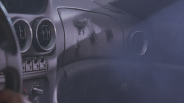 close angle of bullet holes punctured in dashboard of car. could be sports car interior. see driver's hand on steering wheel. - 弾丸点の映像素材/bロール