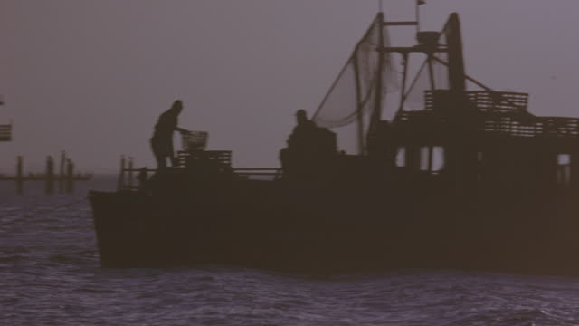 wide angle of waves at sunset. shot pans right, see pier in background. fishing boat anchored in foreground. see two figures on boat. shot continues to pan right, see small motorboat driving from right to left toward fishing boat. motorboat drives out of - anchored stock videos & royalty-free footage