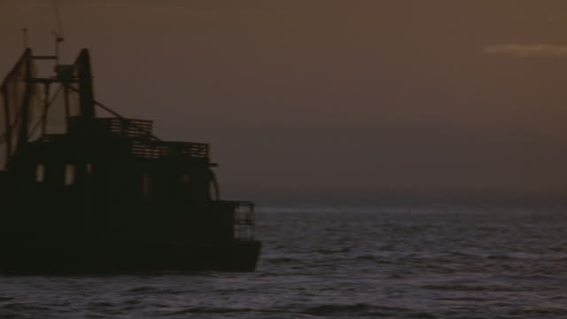 wide angle of waves at sunset. shot pans right, see pier in background. fishing boat anchored in foreground. see two figures on boat. shot continues to pan right, see small motorboat driving from right to left toward fishing boat. shot pans left as motorb - anchored stock videos & royalty-free footage