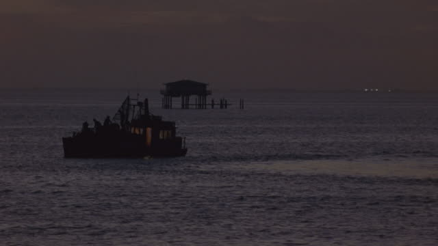 wide angle of fishing boat anchored in ocean. dusk. pier in background. motorboat drives around fishing boat. - anchored stock videos & royalty-free footage