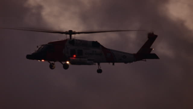 wide angle of u.s. coast guard helicopter flying in air. helicopter circles around in background, hovers in air for a little facing camera, then flies out of shot to left. dusk. - coast guard stock videos & royalty-free footage