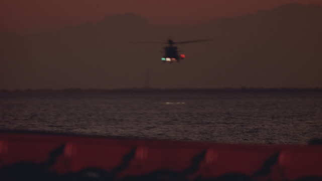 wide angle of u.s. coast guard flying from distance into foreground towards camera. dusk. helicopter flies over shot. cargo dock in foreground. - coast guard stock videos and b-roll footage
