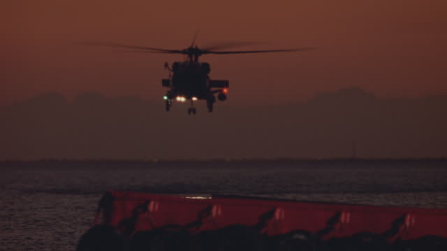 wide angle of u.s. coast guard flying from distance into foreground towards camera. dusk. helicopter flies over shot. cargo dock in foreground. - guardia costiera video stock e b–roll