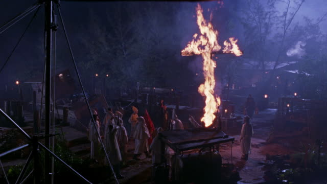 wide angle of members of the ku klux klan congregating together by boat dock.  performing ritual of  burning cross and chanting. shot pans up and down of ritual from distance behind boats. fires. - ku klux klan stock videos and b-roll footage