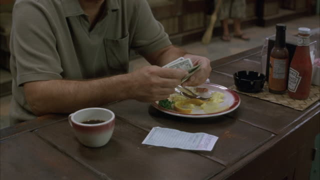 est close angle shot of meal at restaurant bar with man counting money out to pay.  plate has eaten eggs, orange peel, and kale.  cup of coffee on right. heinz ketchup and hot sauce on left side of man. - ketchup stock videos and b-roll footage