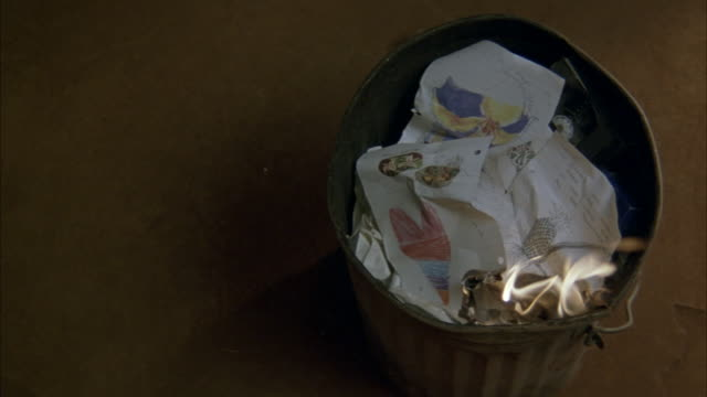 CLOSE ANGLE LOOKING DOWN ON GARBAGE CAN. INFLAMED CRUMPLED PIECE OF PAPER IS THROWN INTO GARBAGE CAN FROM LEFT SIDE OF SCREEN LIGHTING THE CONTENTS OF GARBAGE CAN ON FIRE. CAMERA THEN ZOOMS IN AS THE FIRE GETS BIGGER.
