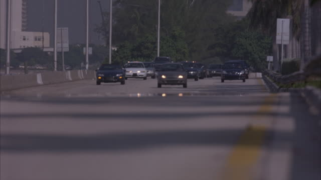 WIDE ANGLE OF SEVERAL CARS APPROACHING DOWN FREEWAY. SEE SILVER FERRARI  SWERVING THROUGH TRAFFIC BEING CHASED BY SEVERAL POLICE CARS AND UNDERCOVER POLICE CARS. SEE ARMED MAN STICK HEAD AND GUN OUT WINDOW OF FERRARI AT END.