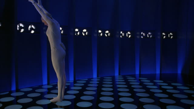 medium angle of stunt.  blonde woman dressed in white, body-fitting suit backflips across blue lighted room. room could be futuristic vault or spaceship. - razzo spaziale video stock e b–roll