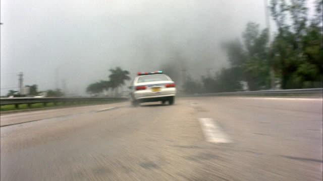 medium angle of car upside-down on fire in middle of highway. see police car with bizbars flashing drive past wreckage. pov follows police car and black sedan through smoke, swerves in and out of cars. pov spins around and stops. see palm trees lining hig - police car stock videos and b-roll footage