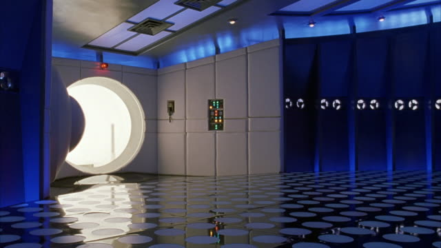 medium angle of futuristic vault or spaceship.  blonde woman  in white, body-fitting suit back flips across blue lighted room. - indoors stock videos & royalty-free footage