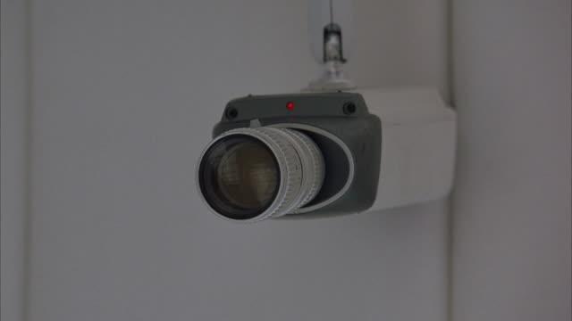medium angle of security camera pointing towards frame left. - telecamera di sorveglianza video stock e b–roll