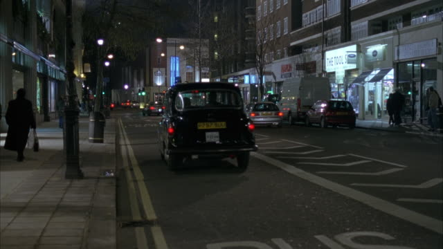 wide angle of london city street with taxis and cars driving down street from right fg to left bg. pedestrians walking on sidewalks of storefronts. - 2004 stock videos & royalty-free footage