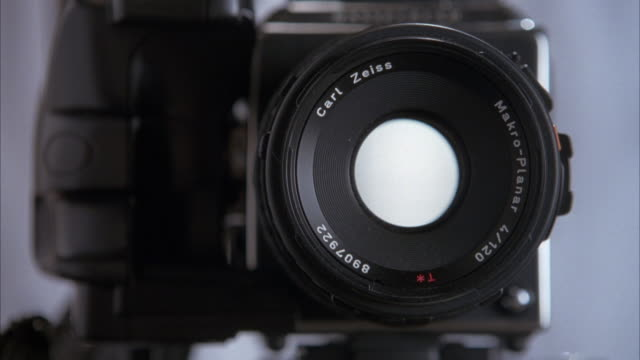 close up angle of an xlr camera with a carl zeiss lens. shutter closes and opens 5 times as if taken a photograph. see right hand with wrist watch reach on top of camera as if pressing button to take photograph. - shutter stock videos & royalty-free footage