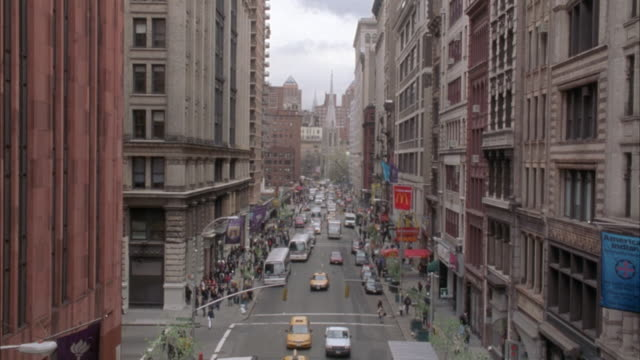 """pan up from city street with traffic to apartment building. city street has many cars and pedestrians walking along side of street. matching dx/nx 2280-012 to 2280-056. condominiums. upper class.<p><a href=""""https://www.sonypicturesstockfootage.com/footage - https stock videos & royalty-free footage"""
