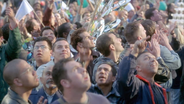 vidéos et rushes de medium angle. crowd looking at something above camera. start pointing and clapping. crowd turns around facing away from camera still clapping. then they scatter in panicked frenzy. possibly at a festival or parade. - terrifié