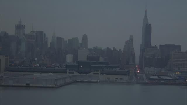 aerial. new york city skyline in bg. flying towards high rise buildings - anno 2001 video stock e b–roll
