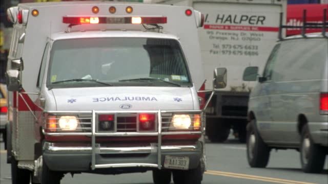 medium angle. looking down city street. camera focused on ambulance as it passes from l-r. 'cabrini ambulance' written on side of ambulance. - ambulance stock videos & royalty-free footage