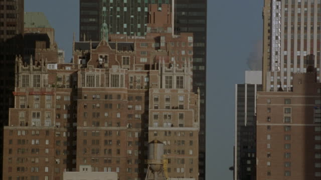wide angle. est. top of brick apartment building in new york city. tudor city apartment buildings. penthouses. midtown manhattan. upper class. - tudor stock videos and b-roll footage