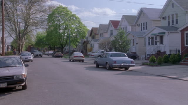 "wide angle of two story, middle class, suburban tract houses on a  street lined with cars. 1973 oldsmobile delta 88 sedan drives down street and pulls into driveway. matching dx/nx shots 2281-025 to 2281-057.<p><a href=""https://www.sonypicturesstockfootag - tract housing stock videos & royalty-free footage"