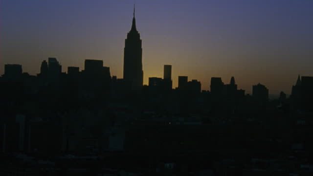 aerial over the new york city skyline at sunset. camera zooms in to the empire state building. - anno 2001 video stock e b–roll