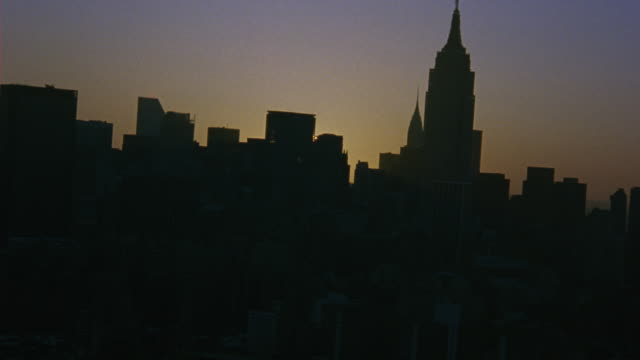 aerial over new york city focusing on the new york city skyline during sunset. camera slow pans to the empire state building. - anno 2001 video stock e b–roll