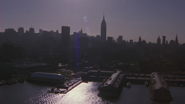 aerial shot of new york city skyline taken from the water. docks in the fg and the skyscrapers lining the bg. occasional sun flares. - anno 2001 video stock e b–roll