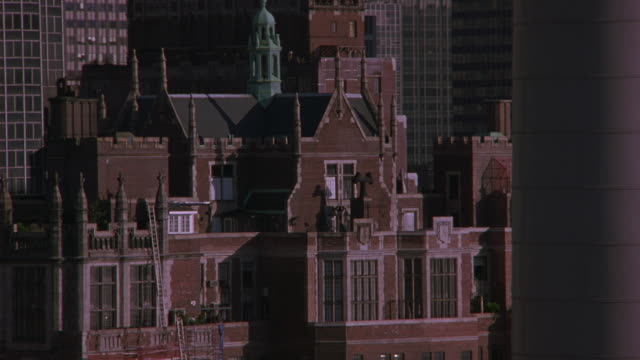 aerial shot flying over new york city circling around a large building with spires and ramparts. might be a hotel or apartment building. tudor city apartments, penthouse. upper class. con edison smoke stack in fg. midtown manhattan. east side. brick build - tudor stock videos and b-roll footage