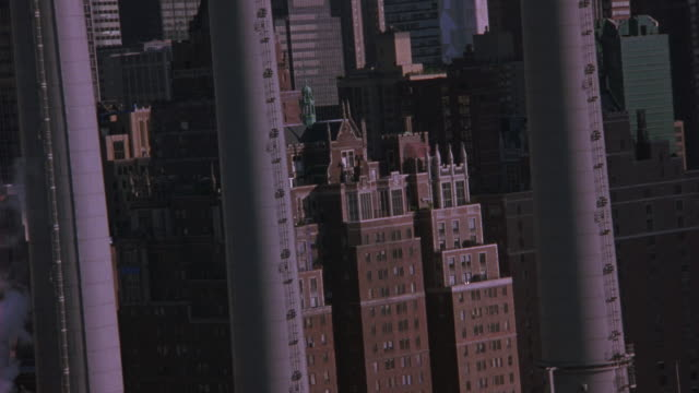 aerial flying circles over brick apartment building with ramparts and spires, weather vane. could be hotel. tudor city apartments, penthouse. upper class. con edison smoke stack in fg. midtown manhattan. east side. brick buildings. - tudor stock videos and b-roll footage